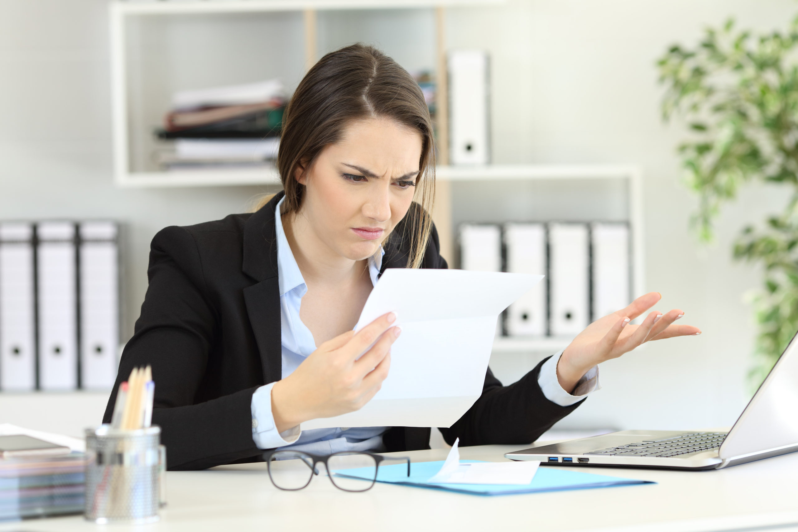 Business woman with document looking confused wondering if her insurer will pay out her claim