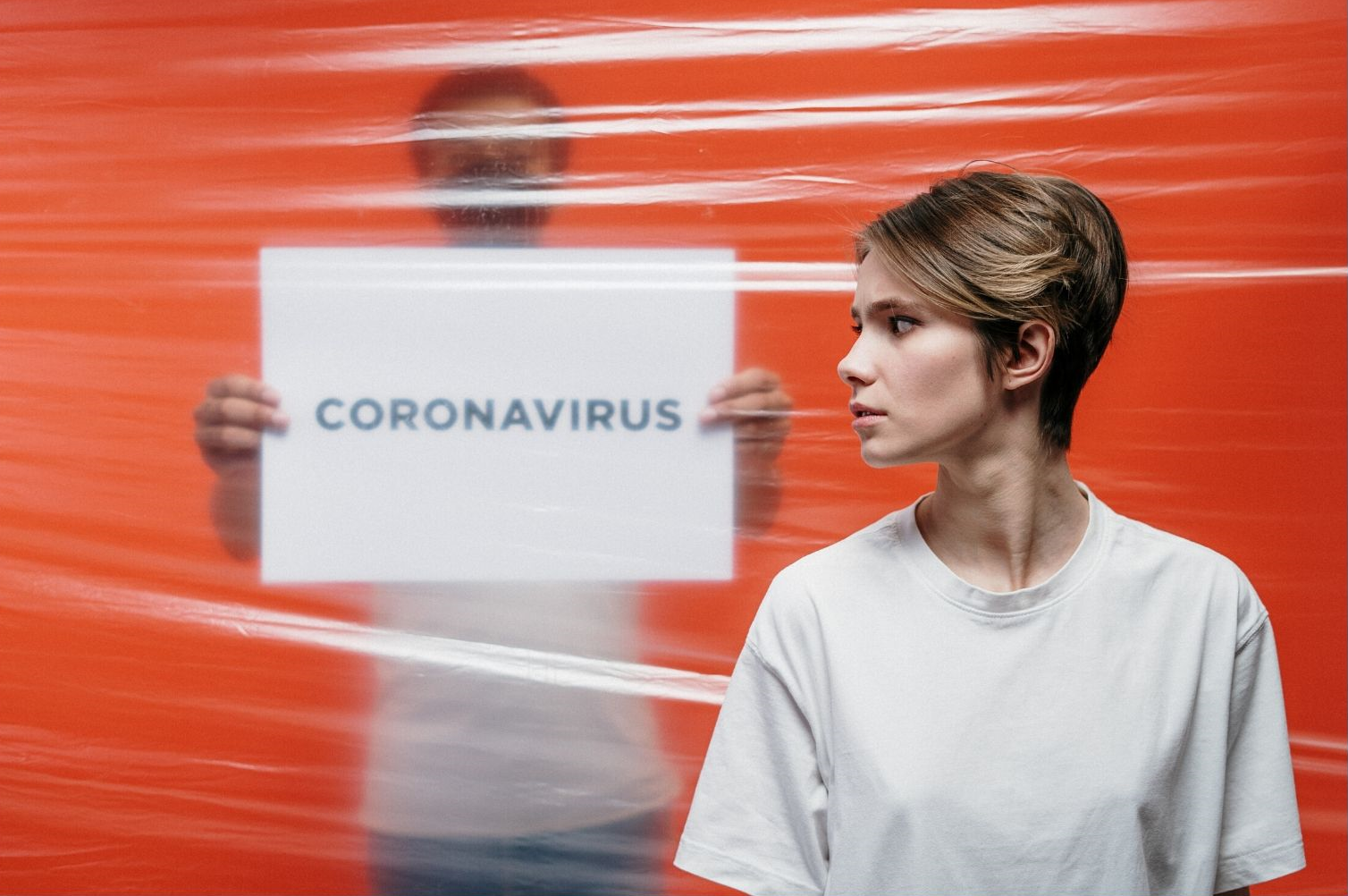Lady worried looking back at coronavirus sign - whether her insurer will pay covid claims.
